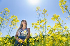 Cute woman in a yellow flowers field. On a warm summer day. Summer fun concept Royalty Free Stock Photo