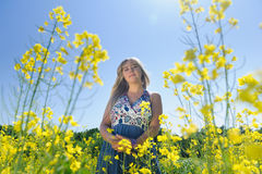 Cute woman in a yellow flowers field. On a warm summer day. Summer fun concept Royalty Free Stock Photos
