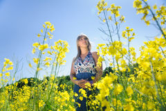 Cute woman in a yellow flowers field. On a warm summer day. Summer fun concept Royalty Free Stock Image