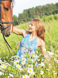 Cute women  with her horse in blossom field Stock Image