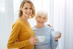 Joyful friendly relatives drinking tea and being in a good mood. Cute women. Lovely pleasant cheerful women standing next to the window with a cup of tasty hot Stock Photos