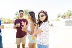 Young Woman With Beer At Summer Party. Cute women smiling while enjoying music festival with friends on weekend royalty free stock images
