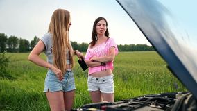 Cute women standing near opened hood of broken car stock footage