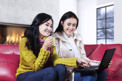Cute women using notebook computer on sofa Royalty Free Stock Photos
