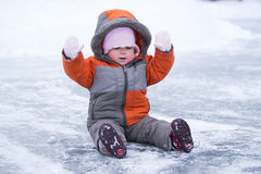 Cute wondered baby sit on lake's ice Stock Photography