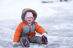 Cute wondered baby sit on lake's ice and smile Royalty Free Stock Images