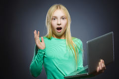 Cute wondering or stressed girl using laptop isolated grey background.  Royalty Free Stock Photos