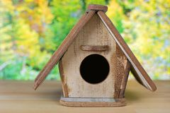 Cute wooden bird house with entrance on wood floor with blurred Royalty Free Stock Images