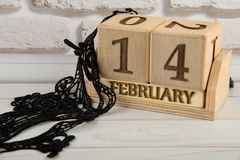 Cute wooden calendar staying on white background and black lace mask laying stock images