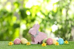 Cute wooden Easter bunny and dyed eggs on green grass. Against blurred background stock photo