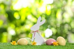 Cute wooden Easter bunny and dyed eggs on grass against blurred background. Cute wooden Easter bunny and dyed eggs on green grass against blurred background stock images