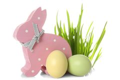 Cute wooden Easter bunny, grass and dyed eggs. On white background royalty free stock images