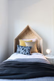 Cute wooden tent style wooden bedhead in a styled children`s bed Stock Images
