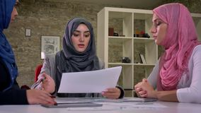 Cute working arab hijab woman are concentration and discussion at common desk, sitting, diverse communication, brick. Background indoor stock video