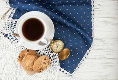 Tea cup. cookies and clock on a wooden whIte textured table, vin. Cute workplace in British style, British motives.Clock and cup tea on the vintage old table Stock Image
