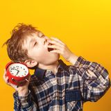 Cute yawning kid holds red alarm clock. Sleepy and yawning schoolboy over yellow wall. Funny boy yawns wide, covering his mouth royalty free stock images