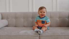 Happy 1 year old baby boy is sitting on sofa, looking into camera and smiles