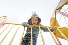 Cute 3 year old boy excitedly plays on a playground. The boy looks at the camera and laughs Royalty Free Stock Photography