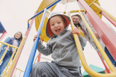 Cute 3 year old boy excitedly plays on a playground. Smiling mother and his siter in the background Stock Image