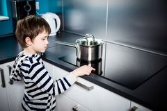 Cute 6 year old boy increases the power of heating. Under the pot on the induction stove Stock Photography
