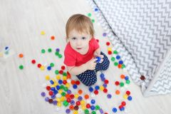 Cute 1 years blue-eyed baby girl plays multicolored meccano at h Stock Photos