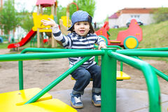 Cute 2 years boy on merry-go-round outdoors Royalty Free Stock Image