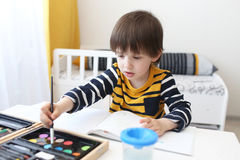 Cute 3 years boy is painting with watercolor Royalty Free Stock Image