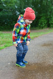 Cute 2 years boy in wellingtons walking after rain Royalty Free Stock Image