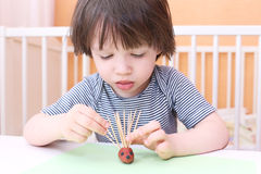 Cute 2 years child made toothpick spines by playdough hedgehog a Royalty Free Stock Images