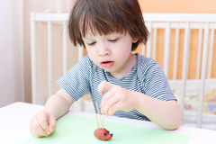 Cute 2 years child made toothpick spines by playdough hedgehog Royalty Free Stock Image