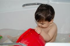 Cute 2 years old baby boy having fun in bathtub. playing with plastic dish in foamy bath.  royalty free stock photo