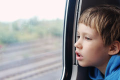 Cute 6 years old boy. Looking through the window Royalty Free Stock Photo