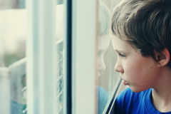 Cute 6 years old boy. Looking through the window Stock Image