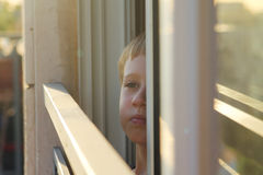 Cute 7 years old boy looks out the window Stock Images