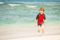 Cute 7 years old boy in red rushwest swimming suit enjoing summer time at tropical beach with white sand and green ocean Royalty Free Stock Photo