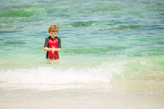 Cute 7 years old boy in red rushwest swimming suit at tropical beach with white sand and green ocean Royalty Free Stock Photos