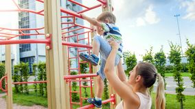 Cute 3 years old toddler boy climbing up high on the children playghround at park while his mother supports and holds. Cute 3 years old toddler boy climbing up stock photo
