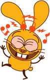 Cute yellow bunny listening to music and dancing Royalty Free Stock Image