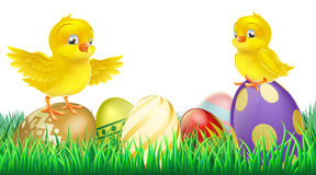 Cute yellow chicks on Easter eggs. Two cute happy little yellow Easter chicks on top of colorful decorated Easter eggs Royalty Free Stock Images
