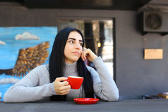 Cute young adult girl smiles, holds mug in hand, looks at camera Stock Photos