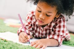 Cute young African American kid girl drawing or painting with colored pencil. Kindergarten children education, back to school, or preschool child study at home royalty free stock photos