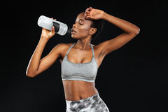 Cute young african american sportswoman standing and holding water bottle Royalty Free Stock Image
