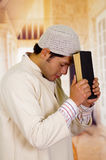 Cute young arabian guy praying to god with a holy book in his hands Royalty Free Stock Photography