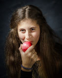 Cute young armenian girl with apple. Cute young armenian girl with red apple on black royalty free stock photos