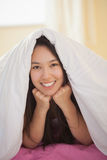 Cute young asian woman under her duvet smiling at camera Stock Photo