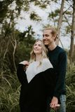 Cute Young Attractive Dating Couple Looking, Smiling, and Laughing in the Dense  Green Tropical Forest Jungle royalty free stock image