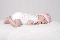 Cute young baby girl. Cute young four week old baby girl lying on blanket with pink woolen hat Royalty Free Stock Photos
