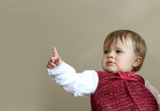 Cute young baby pointing. Half body portrait of cute young baby pointing with studio background Stock Photos
