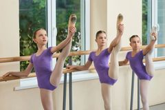 Cute young ballerinas stretching legs. Legs lift of young beautiful ballerinas at ballet barre, window nature background stock photos