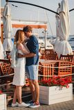 Cute young beautiful couple kissing near to the small summer cafe at port, happy smiling outdoor portrait stock photo